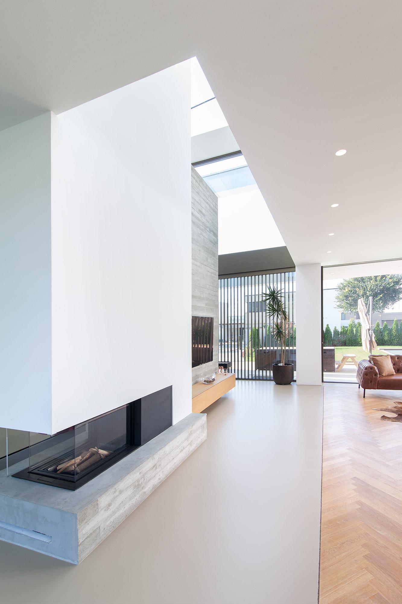 Villa Y Betonwand als Raumteiler mit Kamin im Erdgeschoss FFM-ARCHITEKTEN.